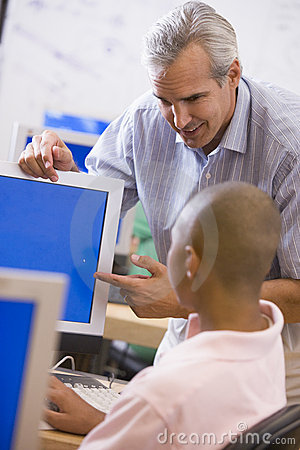 A teacher talks to a schoolboy using a computer