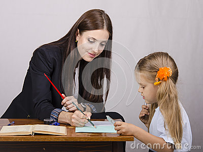 The teacher teaches lessons with a student sitting at the table