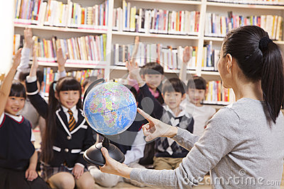 Teacher teaching geography to schoolchildren with a globe