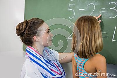 teacher teaching girl on chalkboard in classroom stock photo image