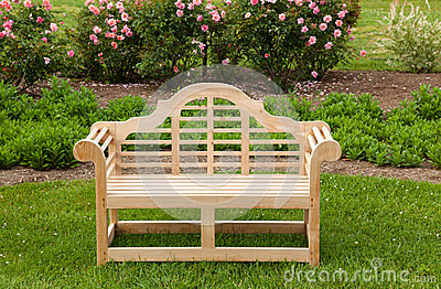 Teak chair or bench on green lawn