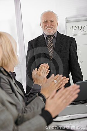 Team applauding senior businessman in office