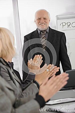 Team applauding senior businessman in office