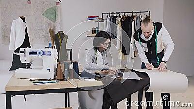 Team Arbeit Hübscher Schneider oder Modedesigner, die in seinem Studio, zeichnende Schablone auf Gewebe arbeiten Kreativ eine Arb stock video footage