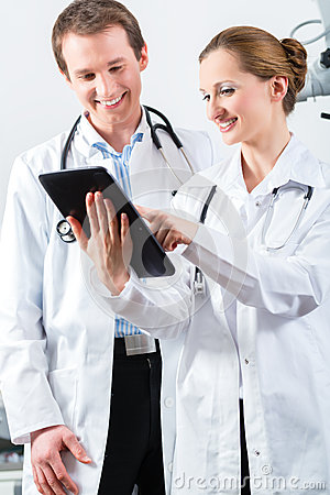 Team of doctors in clinic with tablet computer