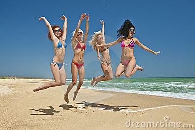 Team of friends jumping at the beach