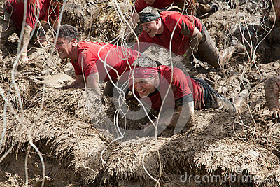 Team of Racers Crawling Through Electric Obsticle Editorial Stock Image