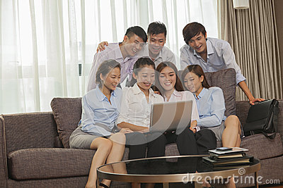 Team of smiling business people working together and looking at one laptop