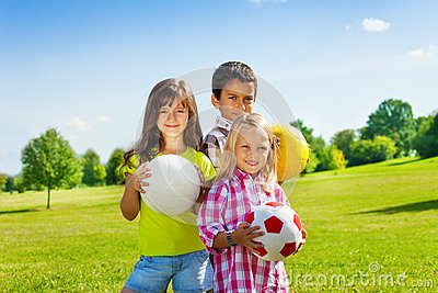 Team of three happy kids with balls