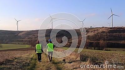 Team van arbeidersmannetje en wijfje De turbines van de wind, geel gebied stock footage