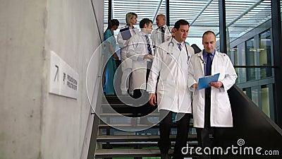 Team von aufeinander einwirkenden Doktoren beim Gehen hinunter Treppe stock video footage