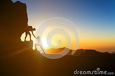 Teamwork couple climbing helping hand Stock Photo