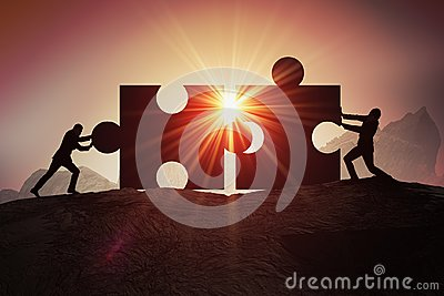 Teamwork, partnership and cooperation concept. Silhouettes of two businessman joining two pieces of puzzle together Stock Photo