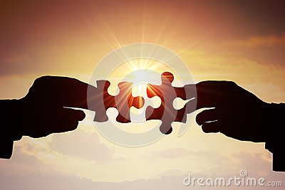 Teamwork, partnership and cooperation concept. Silhouettes of two hands joining two pieces of puzzle together Stock Photo