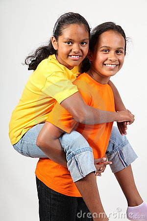 Teamwork piggy back ride by two happy young girls