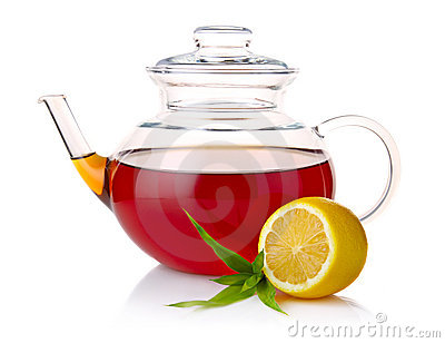 Teapot with black tea, green leaves and lemon