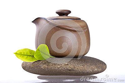 The teapot and fresh leaf on stone