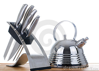 Teapot and a set of knifes on a white background