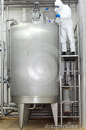 Technician controlling industrial process in tank