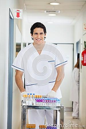 Technician Pushing Medical Cart In Hospital