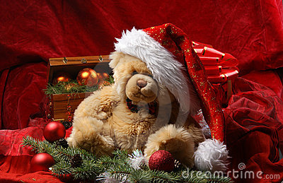 A teddy bear in a Christmas hat on red silk