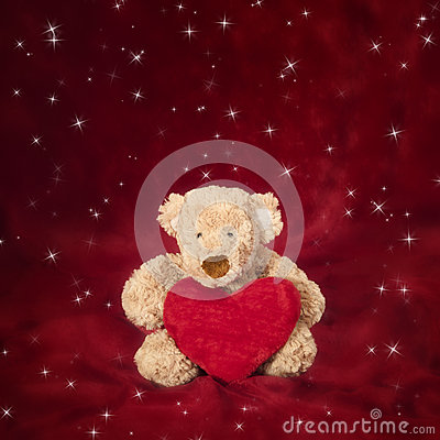 Teddy bear with heart shaped pillow on red
