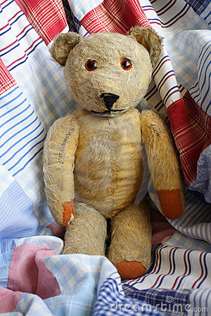 Teddy Bear on a Patchwork Quilt.
