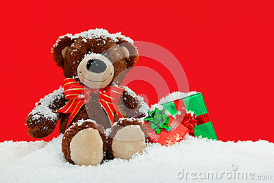 Teddy bear in the snow with gifts