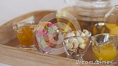 Tee in der Teekanne auf dem Tisch mit Nachtisch in Form von Acajounüssen, Bonbons, kandierten Früchten und Stau stock footage