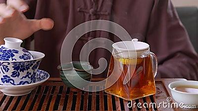 Tee-Meister, der frisch gebrannten Tee aus Gaiwan in Sieb gießt, bis zum Brillenkrug Mann gießt heißes Teegetränk in die Brille stock video