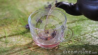 Tee wird in ein Glas von einer Lehmteekanne gegossen Grüner Tee mit Cup und Teekanne stock video