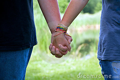 Teen age couple holding hands, summer love