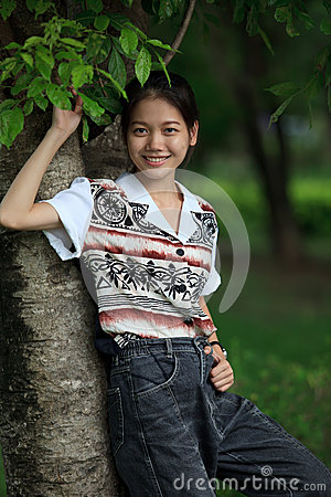 Teen age  standing near tree in the park with ni