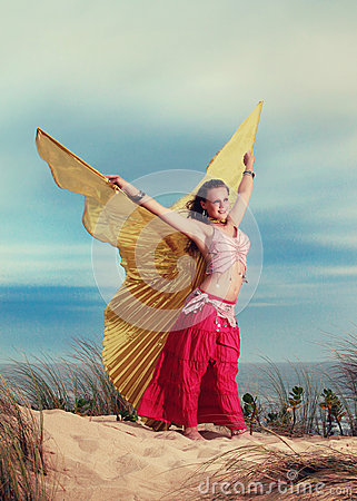 Teen Belly dancer with wings performing on the beach