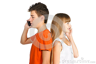 Teen boy and girl chatting on cell phones