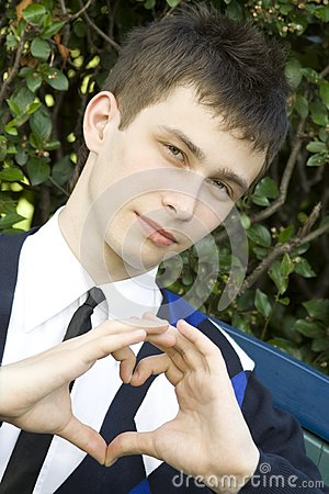 Teen boy making heart shape with hands
