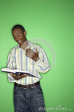 Teen boy reading a book.