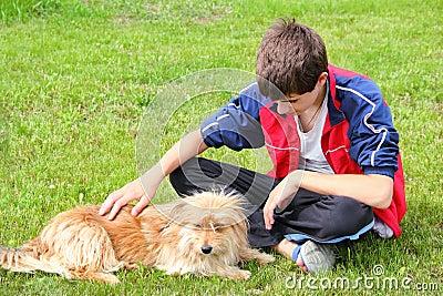 Teen boy stroking his dog