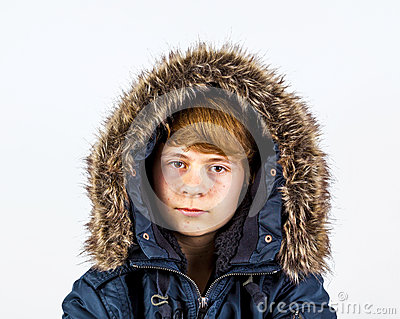 Teen boy wearing an anorak with fake fur around the hood