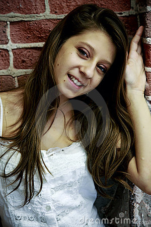 Teen by brick wall