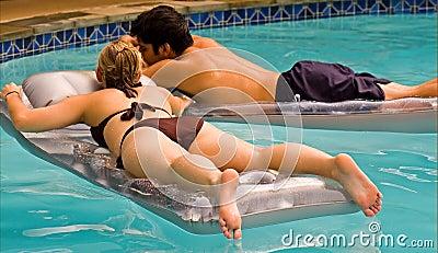 Teen couple floating in pool
