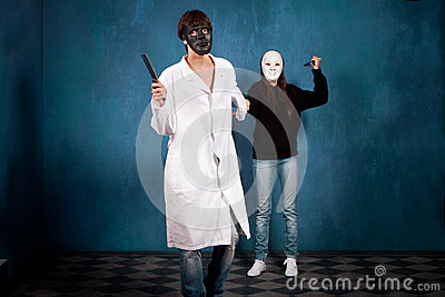 Teen couple with halloween masks and knifes