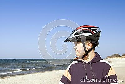 Teen with cycle helmet by sea