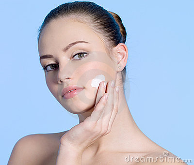 Teen girl applying cream on cheek