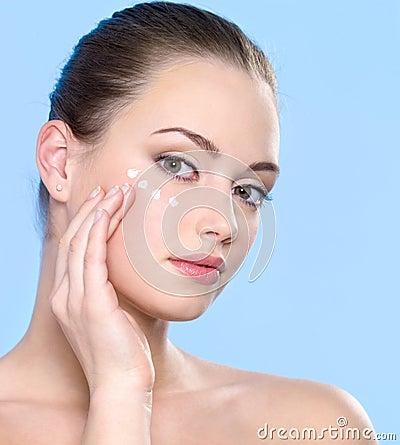 Teen girl applying cream on skin around eyes