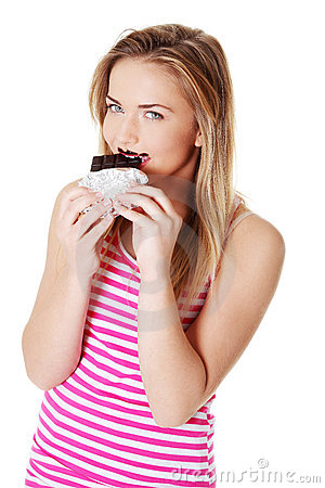 Teen girl biting a chocolate bar.