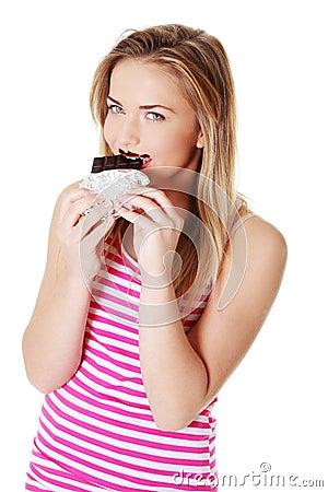 Teen girl biting a chocolate bar.
