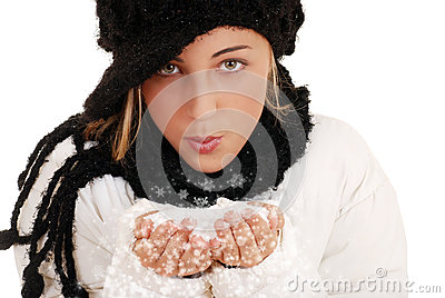 Teen girl blowing snow from hands
