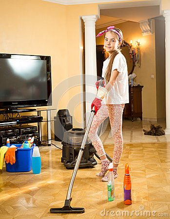 Teen Girl Cleaning Up Floor At Room With Vacuum Cleaner