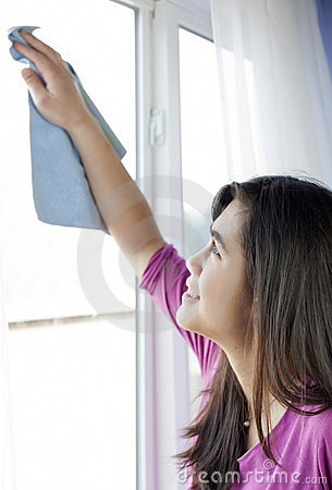Teen girl cleaning windows inside home